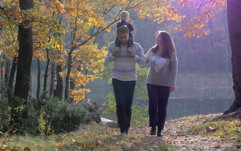 Une famille marchant dans un parc en souriant.