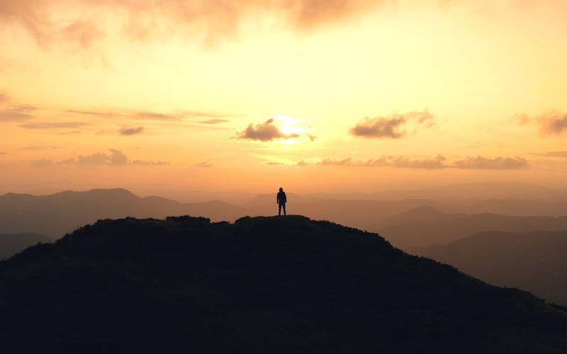 Muž stojí na vrcholku hory poté, co ji zdolal.