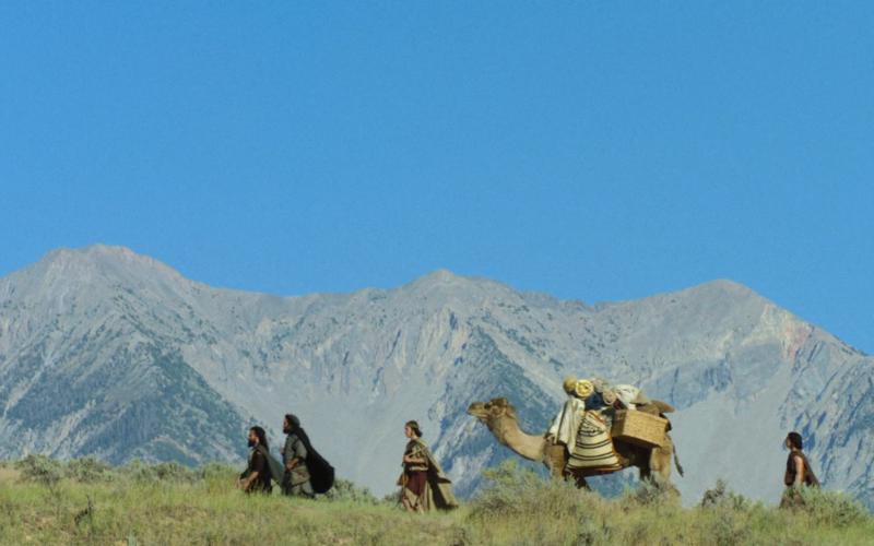 hommes marchant à côté d'un chameau, des montagnes et le ciel bleu en arrière-plan
