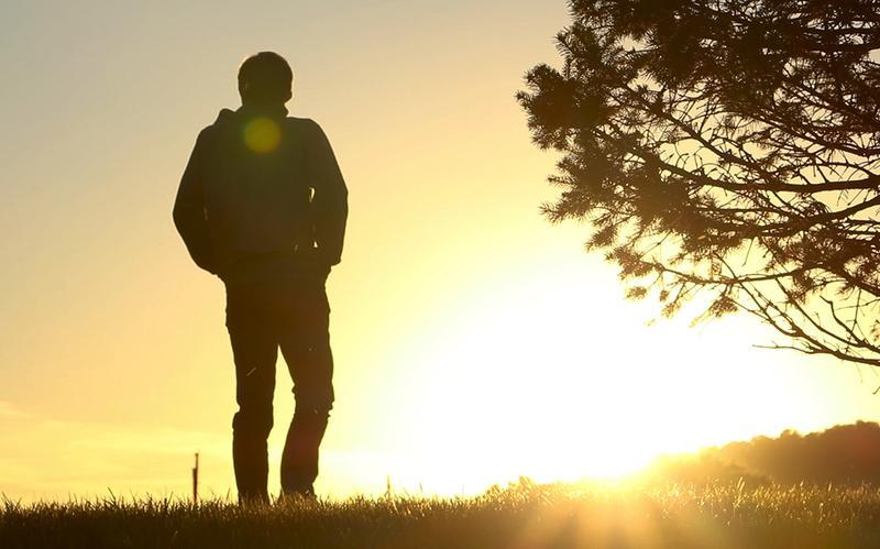 Um Homem pensativo caminha num campo, ao pôr do sol