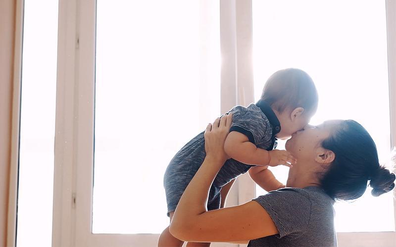 Mamma som kramar och pussar sin bebis.