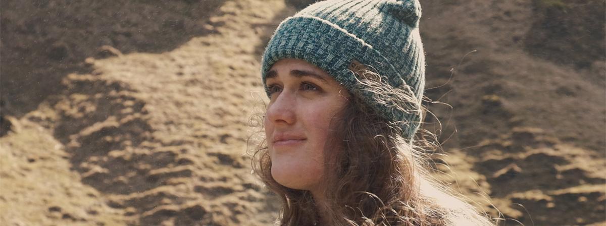 Une jeune fille portant un chapeau regarde au loin avec le sourire.