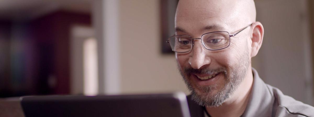 Muškarac se smiješi dok gleda u svoj iPad.