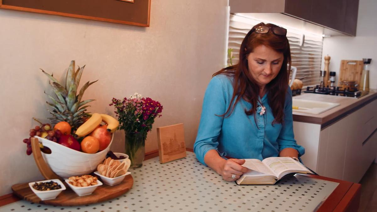 A woman sits at her dining room table and studies the scriptures.