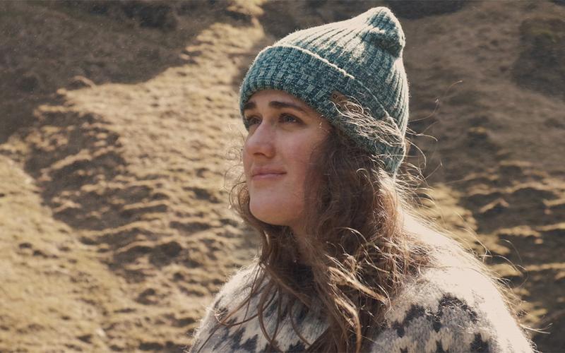 Djevojka nosi šešir i gleda u daljinu smiješeći se.