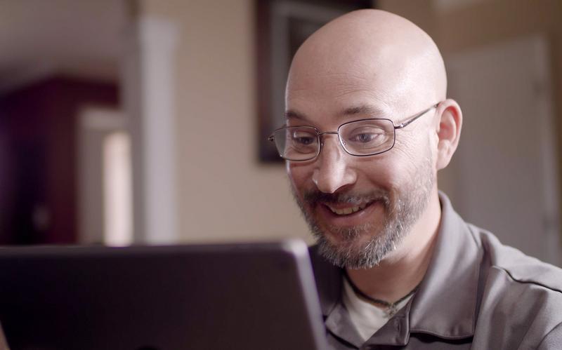 Mosolygó, iPad-et néző férfi