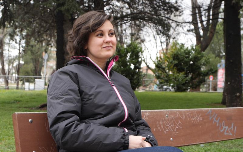 Fiatal nő ül egy padon és elmélkedik.