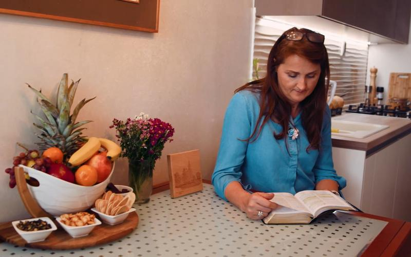 egy nő az ebédlőasztalnál ül és a szentírásait tanulmányozza