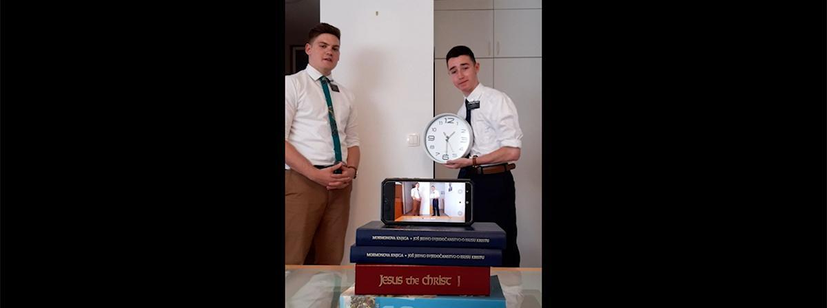 Een jonge man houdt een klok vast terwijl een andere man spreekt.