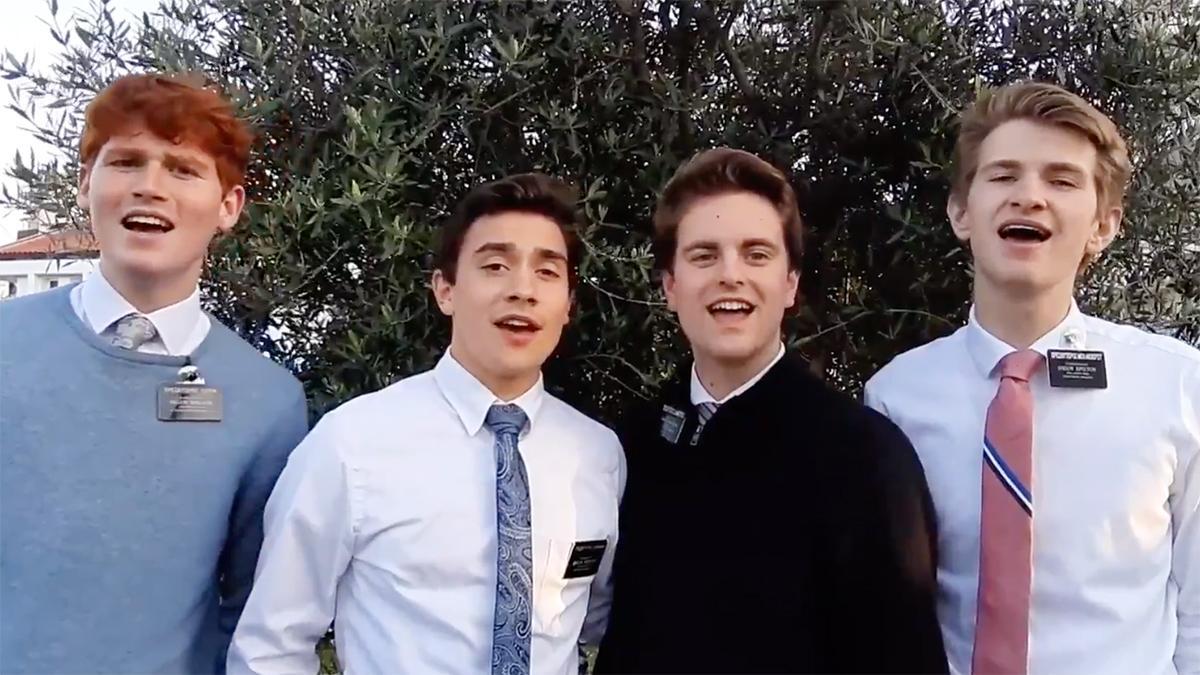 Quatro missionários a cantar num jardim.