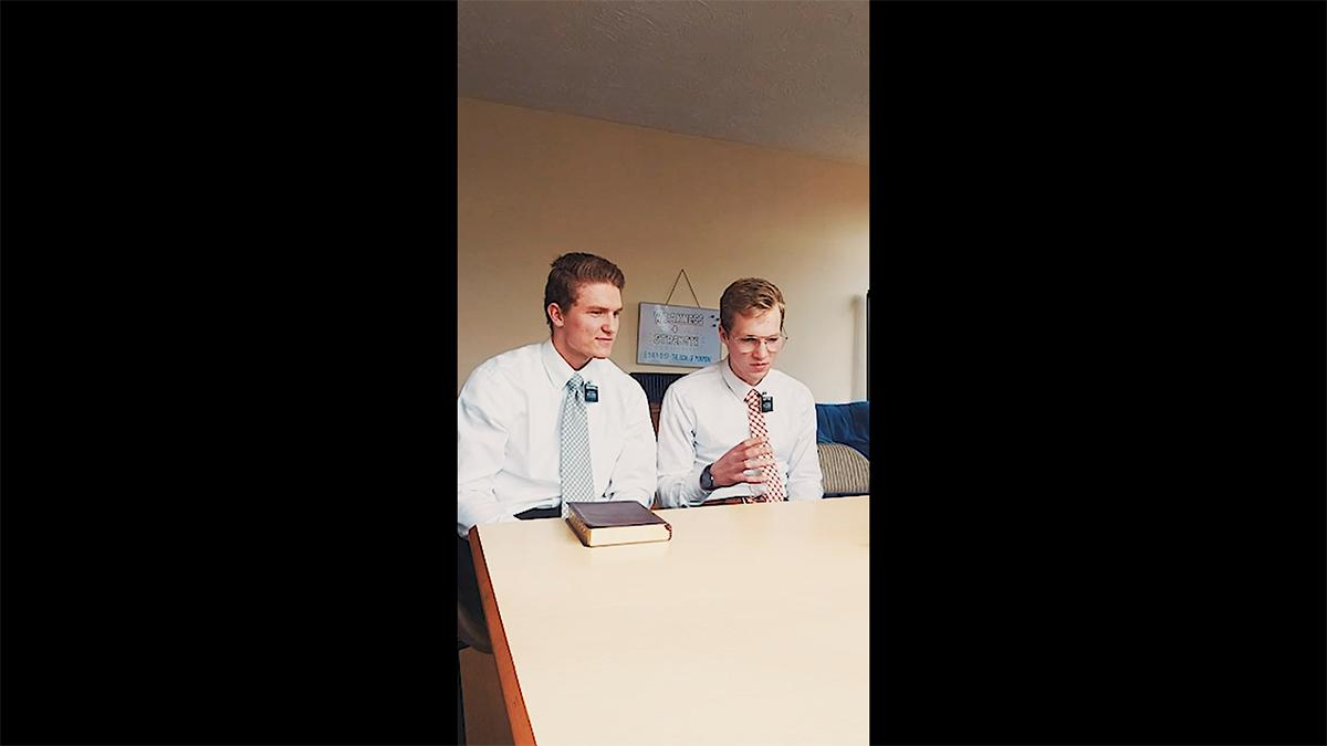 two elder missionaries sit on a table with their Holy Scriptures