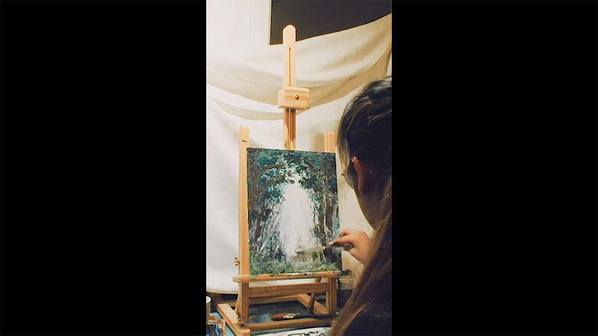 en ung kvinna målar en bild