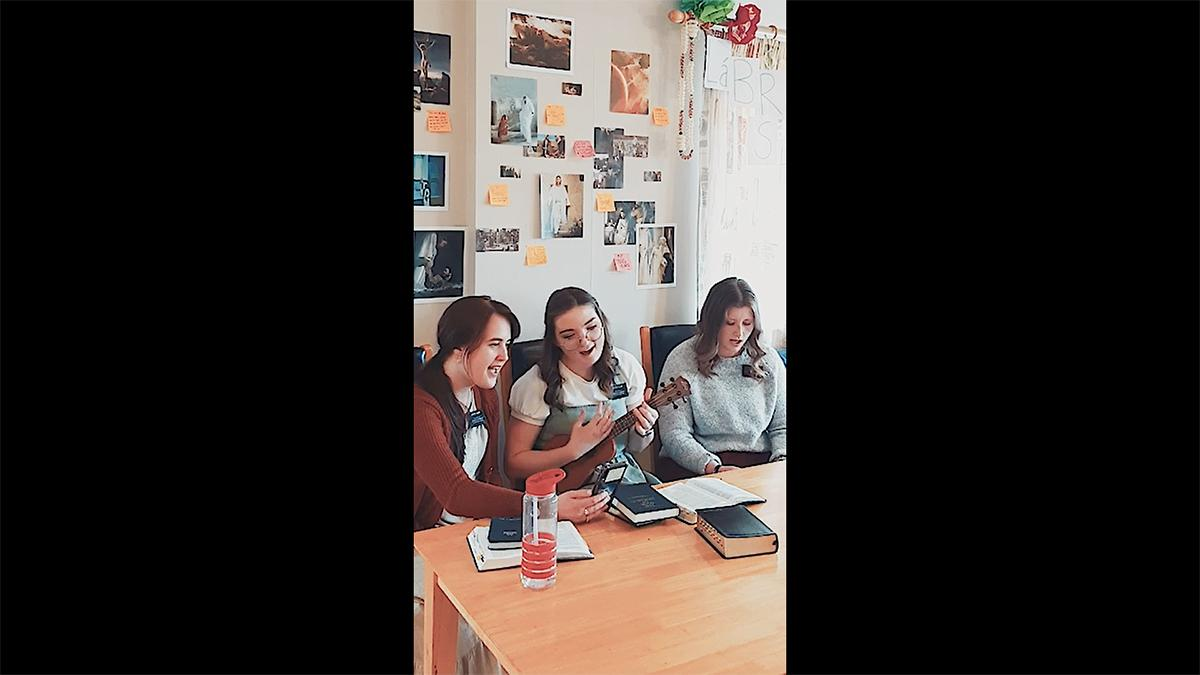 three sister missionaries sing and play the ukulele during an online live devotional