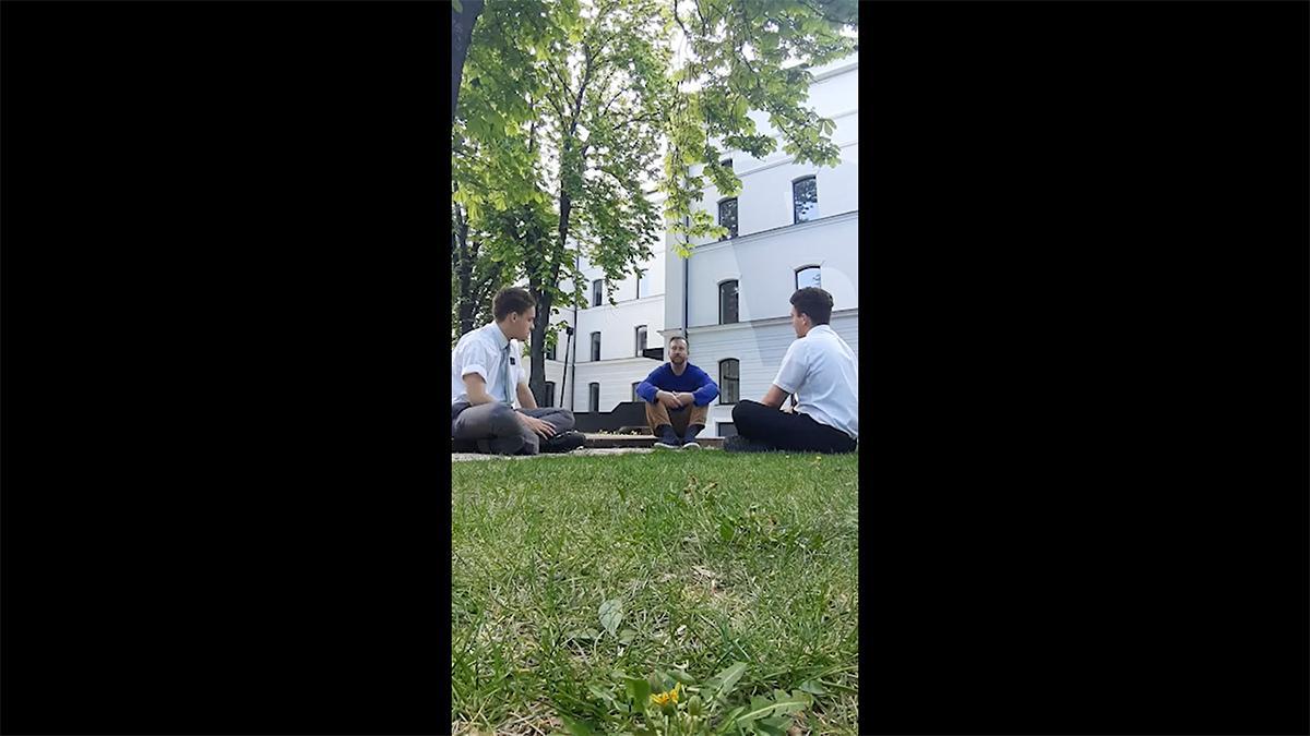 starešini misijonarja sedita na travi in se pogovarjata s prijateljem