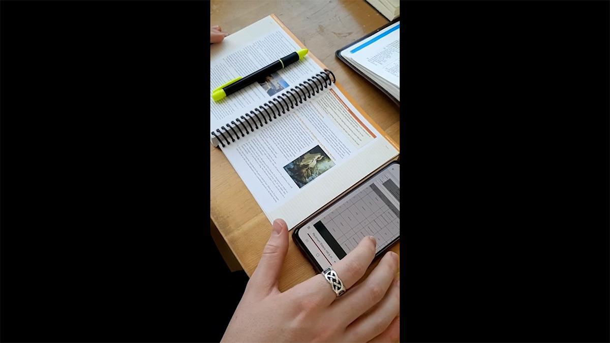 a hand grabs a smartphone on a study table