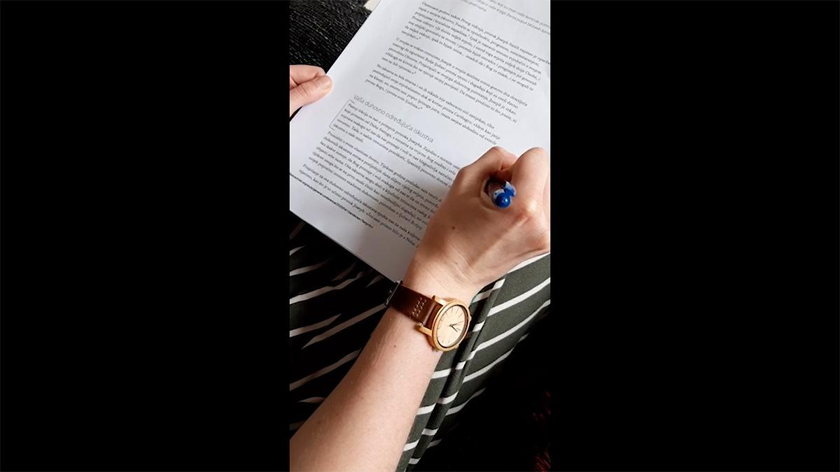 hands hold a paper with text and a pen
