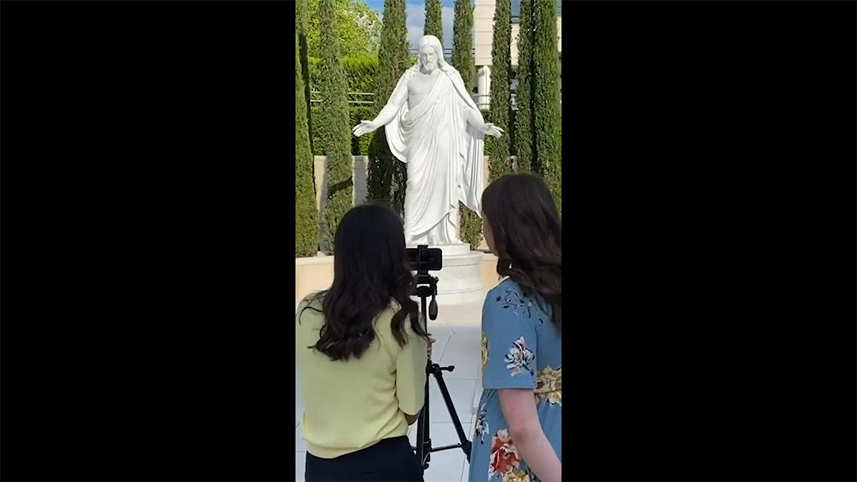 two young women stand in front of a white statue of Christ