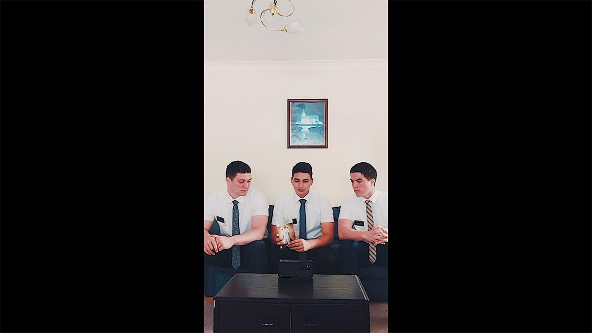 three young men wearing ties sit on a couch and have an online meeting via smartphone