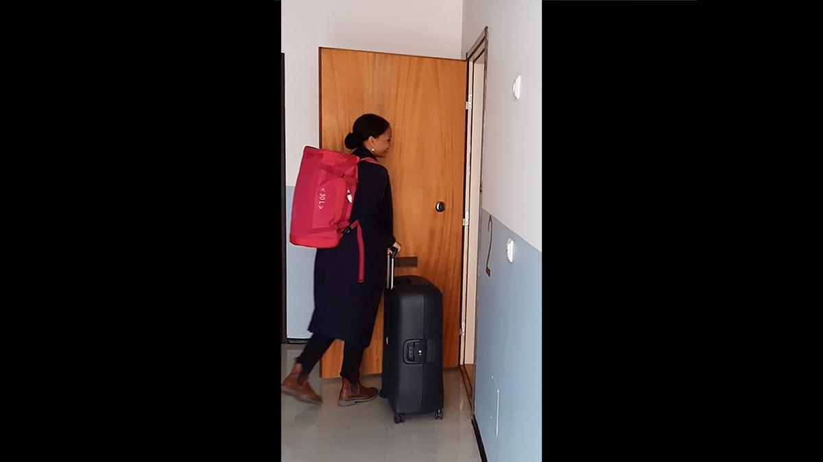 Dekle s kovčkom vstopi v stanovanje.