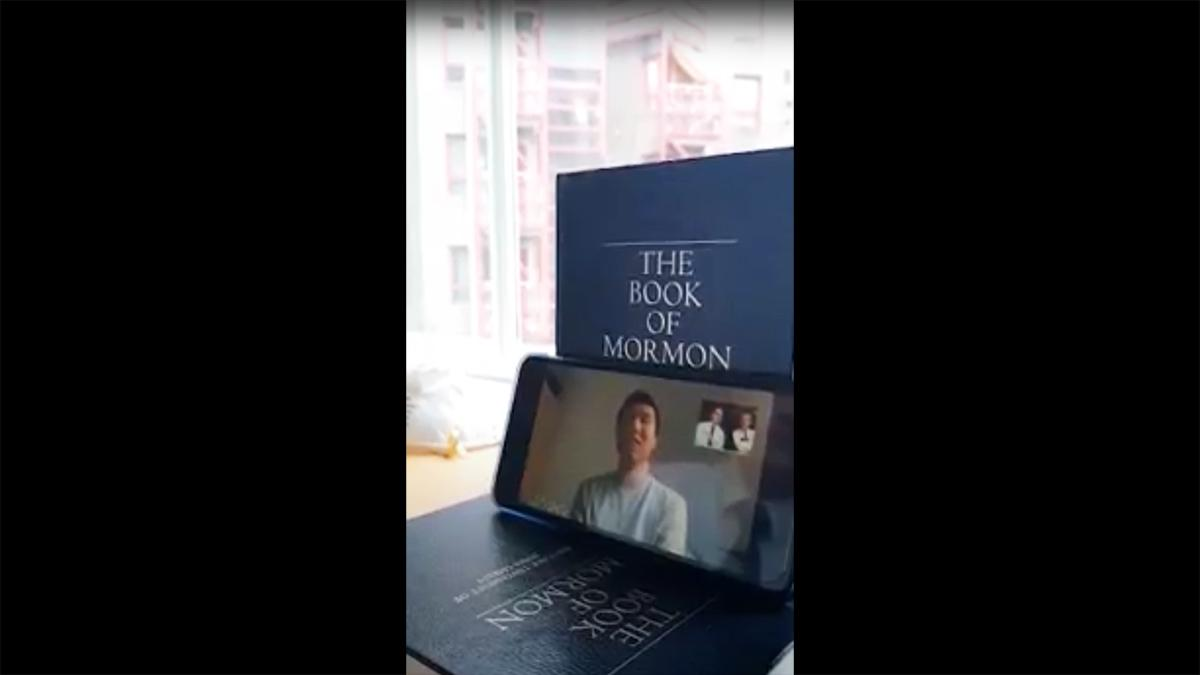 a smart phone is leaning on a book and shows a zoom meeting
