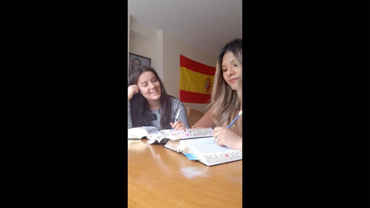two young women sit at a table and study from books