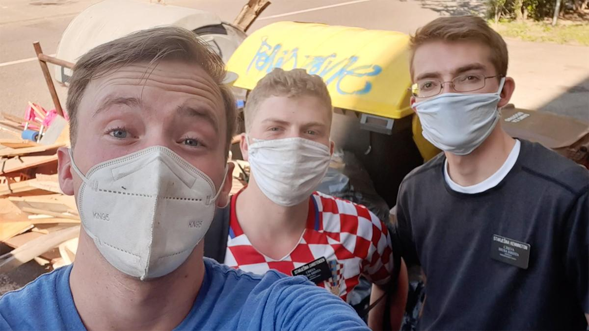 three missionaries wearing face masks are helping with yard work