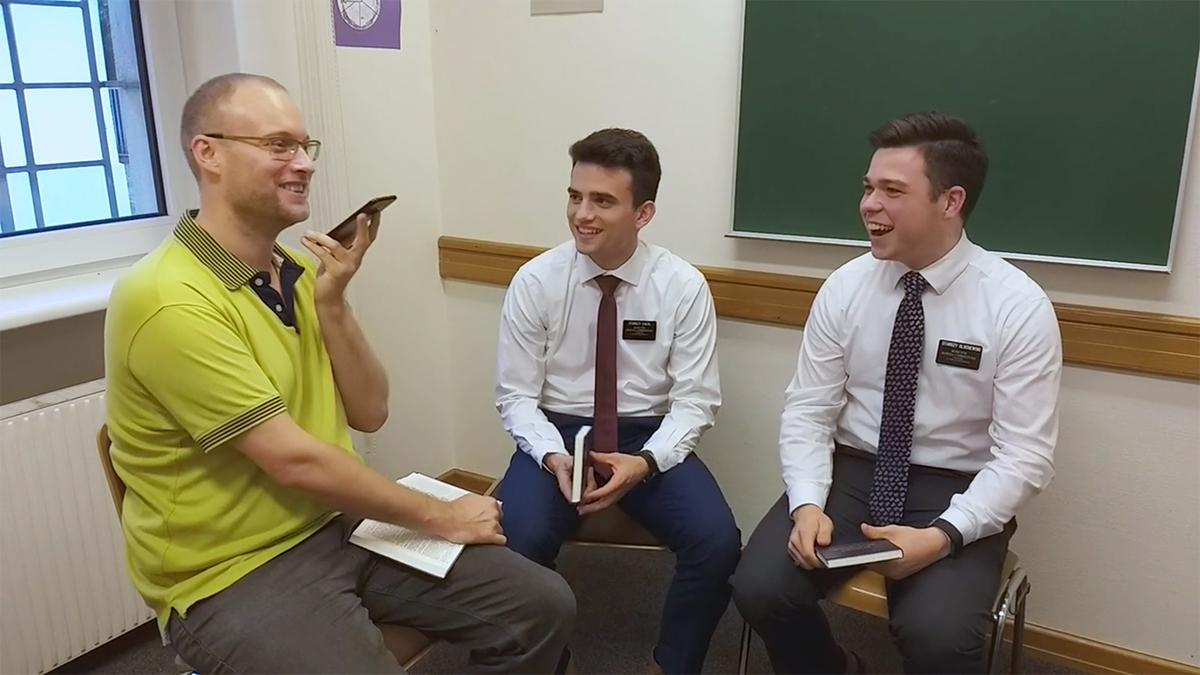two missionaries and a man are talking on the phone