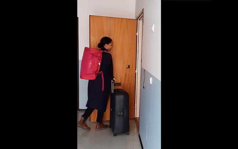 en ung kvinna med resväska går in i en lägenhet
