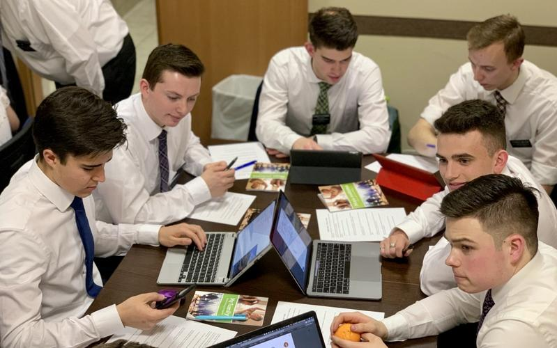 missionaries with laptops around a table