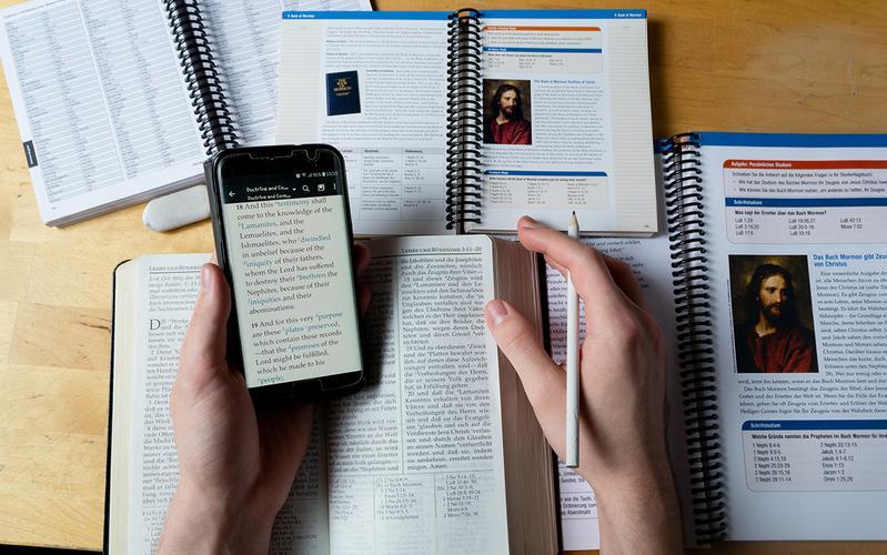 asztal, rajta okostelefonnal, szentírásokkal és kézikönyvekkel