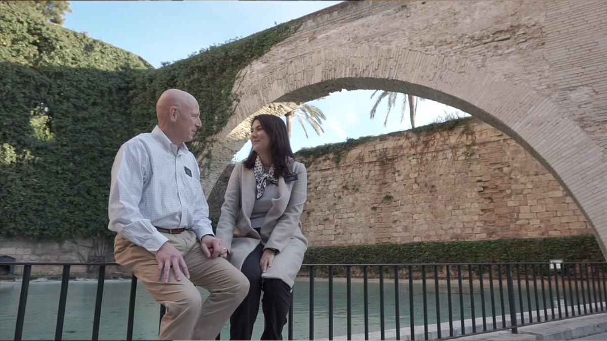 A couple sitting at a bridge.