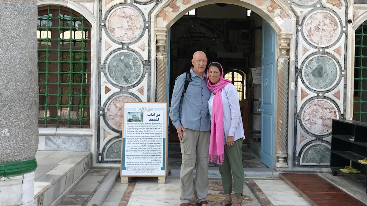 A couple standing in front of a mosque.