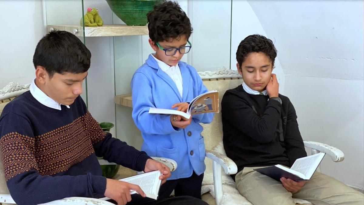 Three boys reading the scriptures.