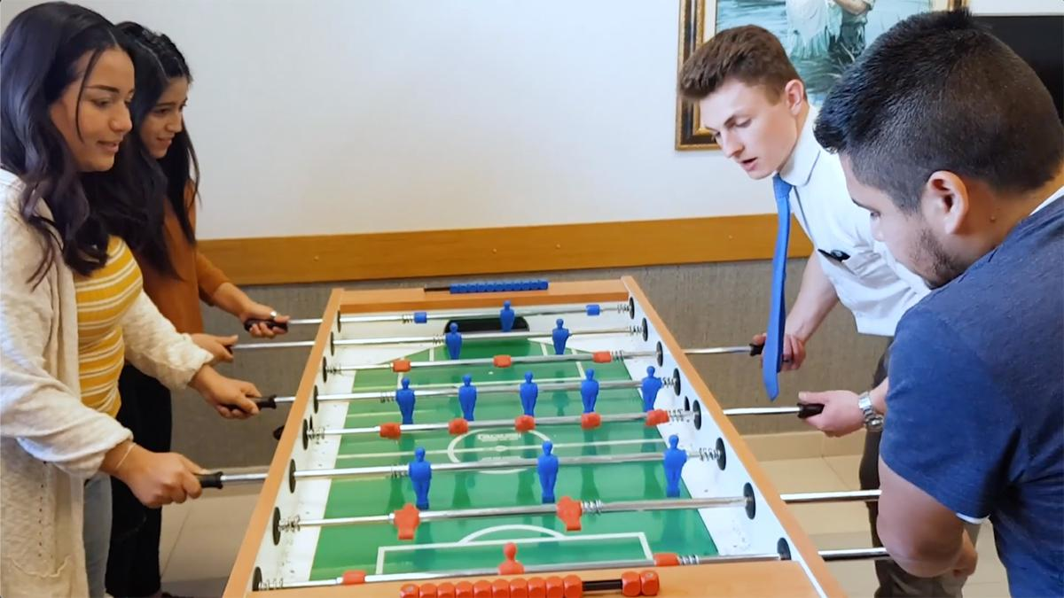 young people are playing table soccer