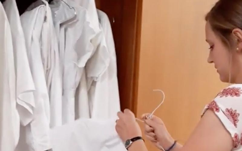 a Sister Missionary is taking baptismal clothes from the cabinet