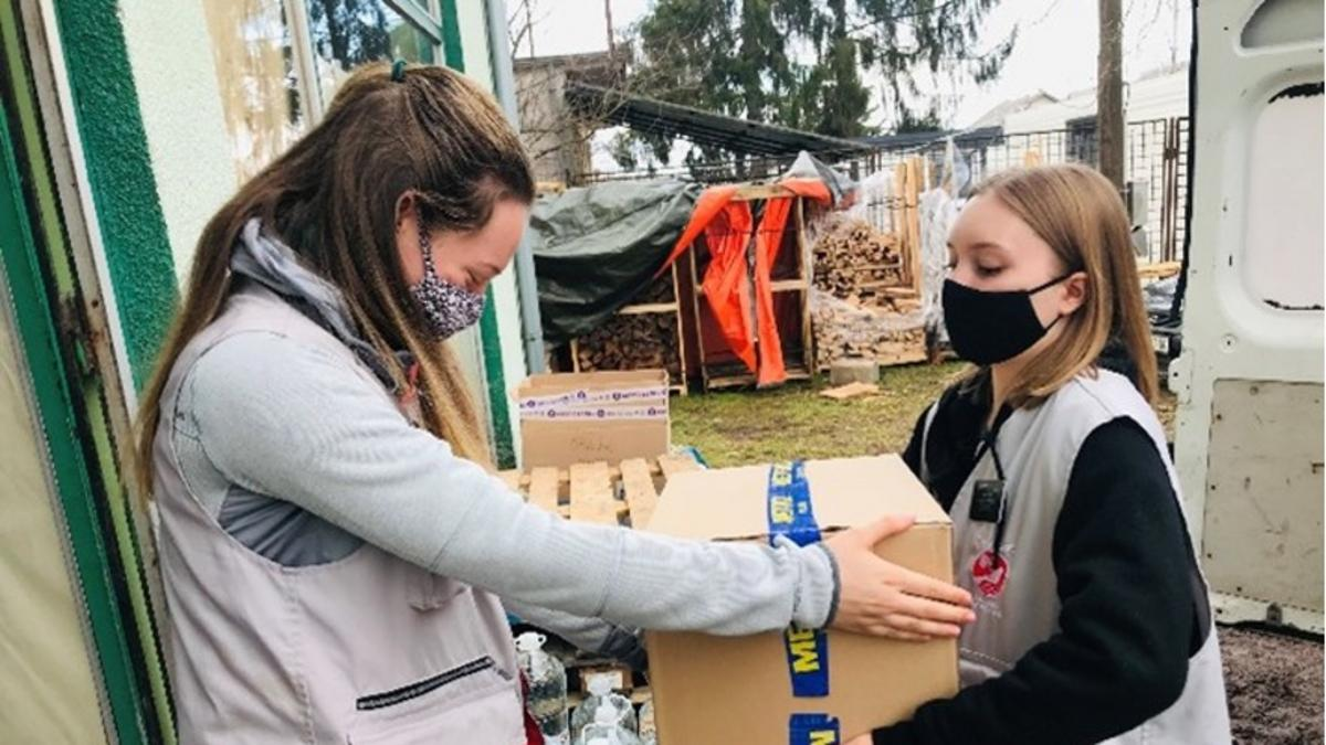 Misijonarji z misijonarskim kombijem razvažajo škatle, polne najnujnejših zalog, v vasi, ki jih je prizadel potres