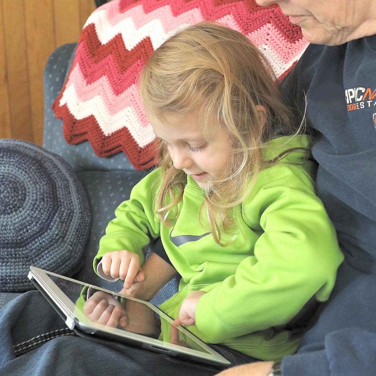 Child and Grandpa are using a tablet