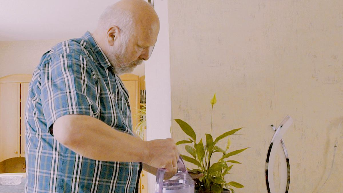 A man is watering a plant