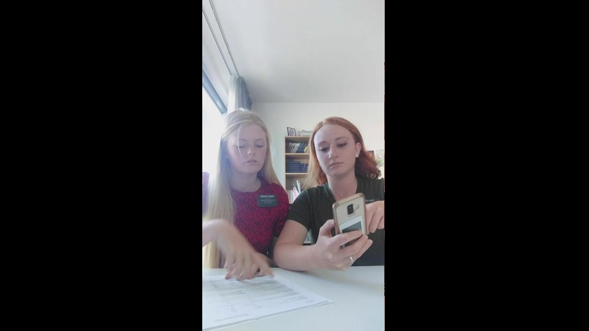 Two smiling Sister Missionaries looking at and sitting in front of a cellphone.