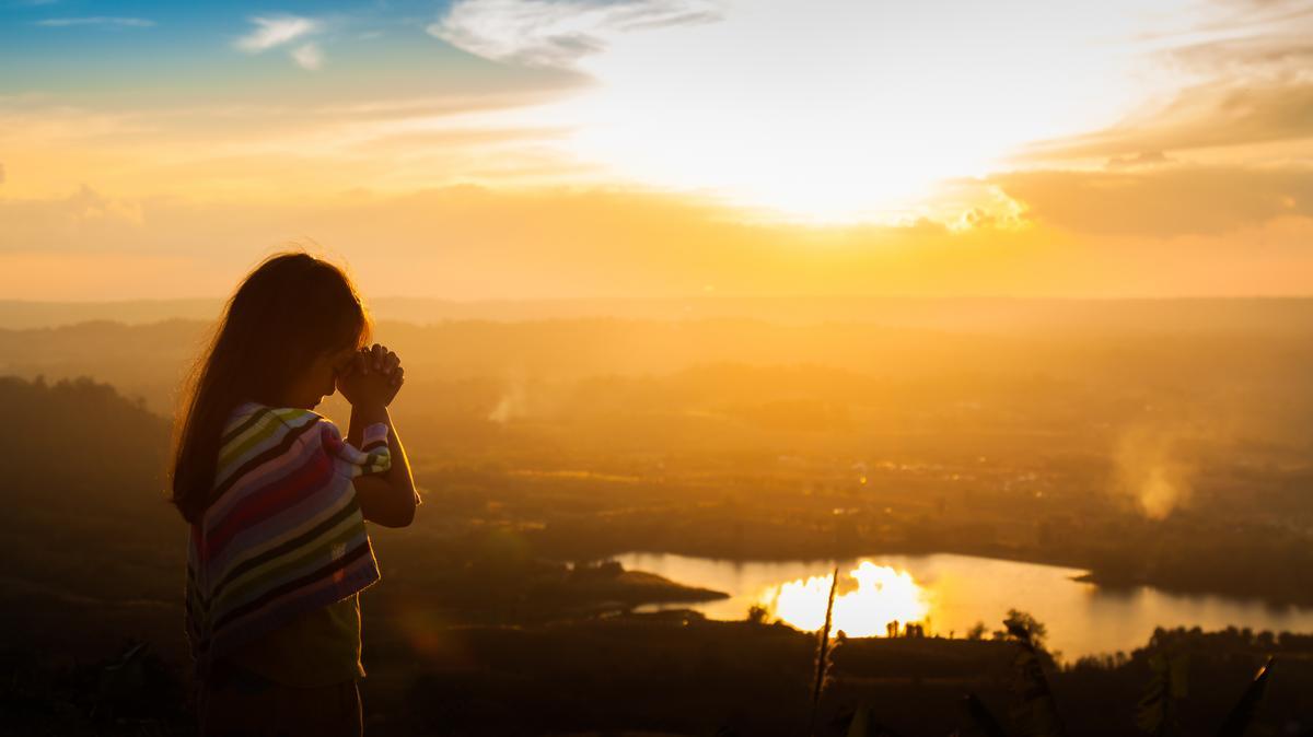 Egy gyermek imádkozik a természetben