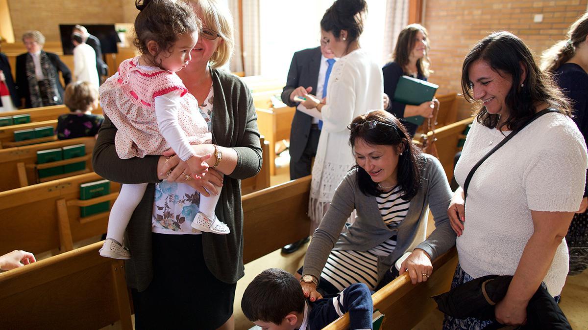 Algunos miembros en una capilla después de una reunión sacramental