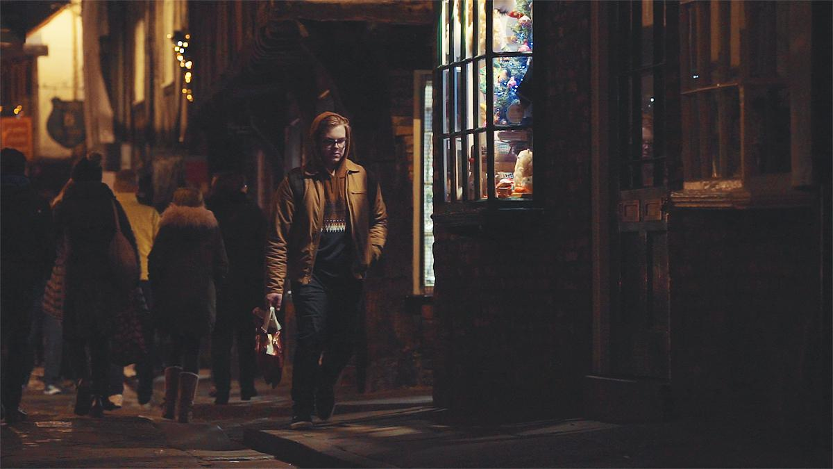 A young man walking down the street at night, at Christmas time.