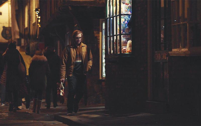 Een jongeman loopt op een avond in de kersttijd over straat.