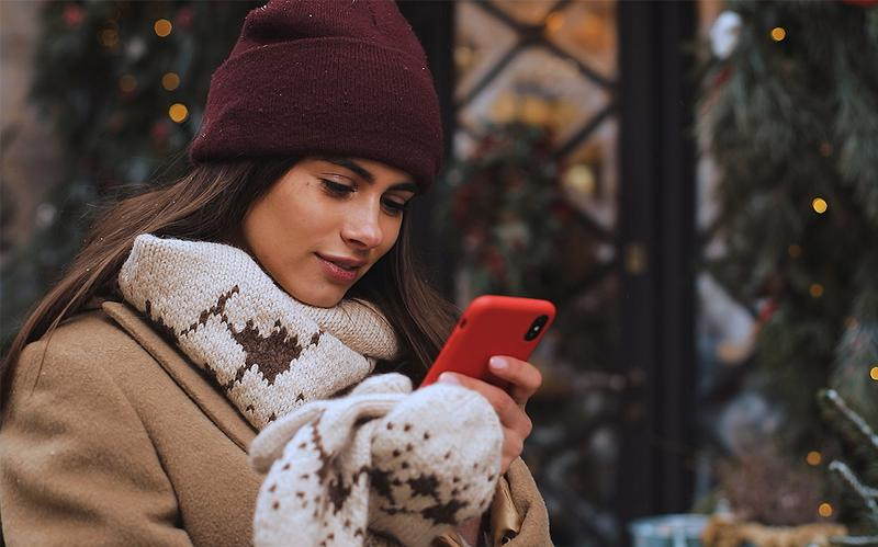 Young woman in Christmas scene sending a text message