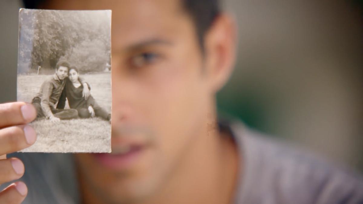 Ein junger Mann zeigt ein Foto seiner Vorfahren