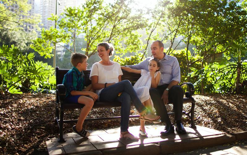 En familie sidder på en bænk