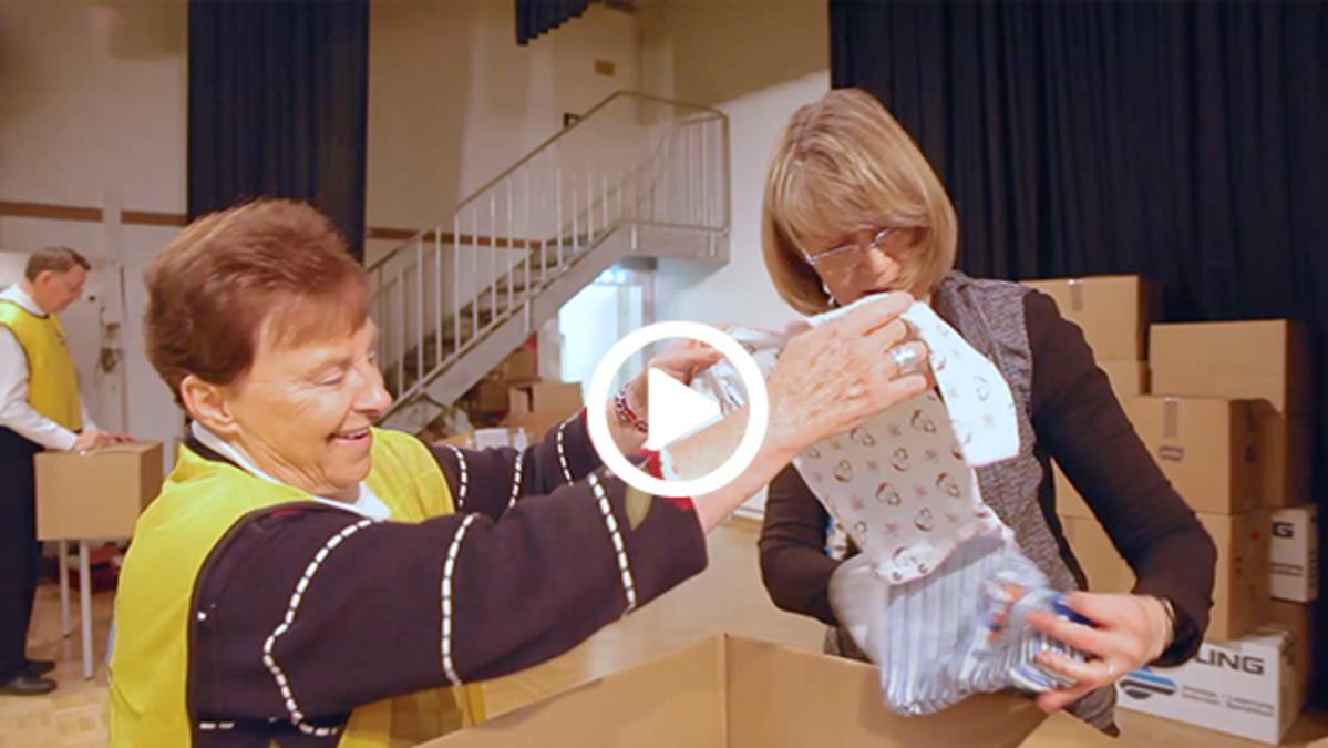 two ladies pack boxes with donations