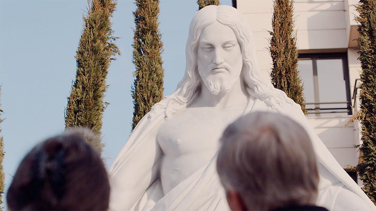 Um casal a olhar para uma estátua de Cristo.
