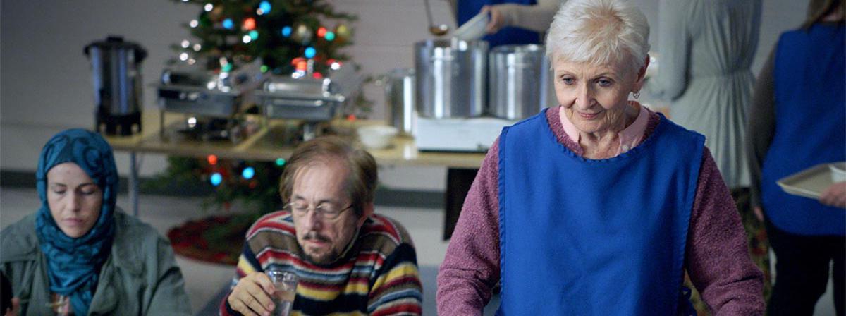 Një grua e moshuar që shërben vullnetarisht në një kuzhinë për të varfrit.