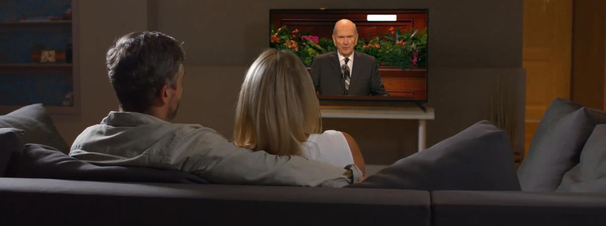 Manželský pár sleduje proslov proroka vtelevizi.
